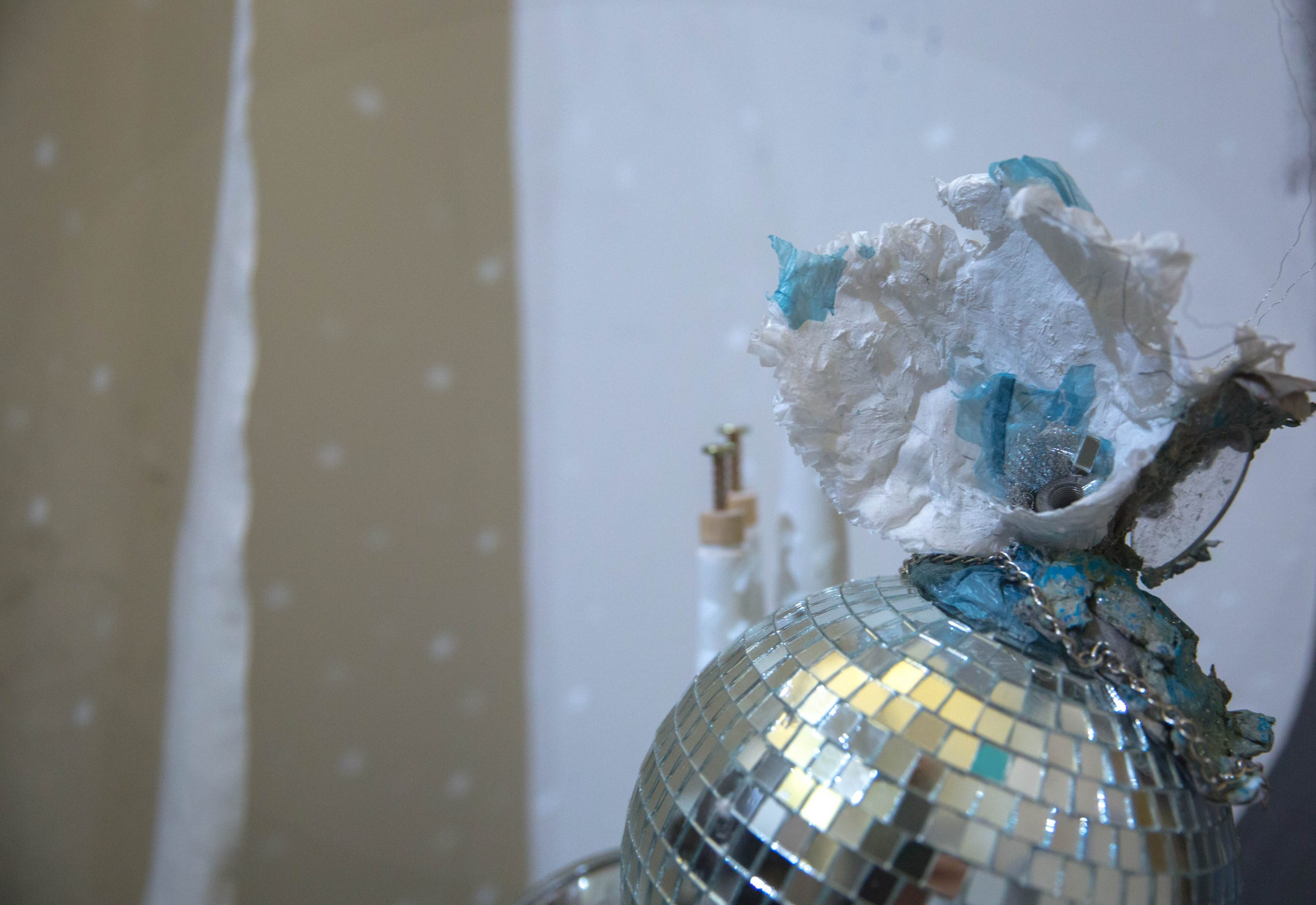 "Globus Purgamentum, 2016, Disco ball, paper pulp, lens from glasses, chain, plastic bags, wire, approx. 12"" in height and 22.5"" in diameter."