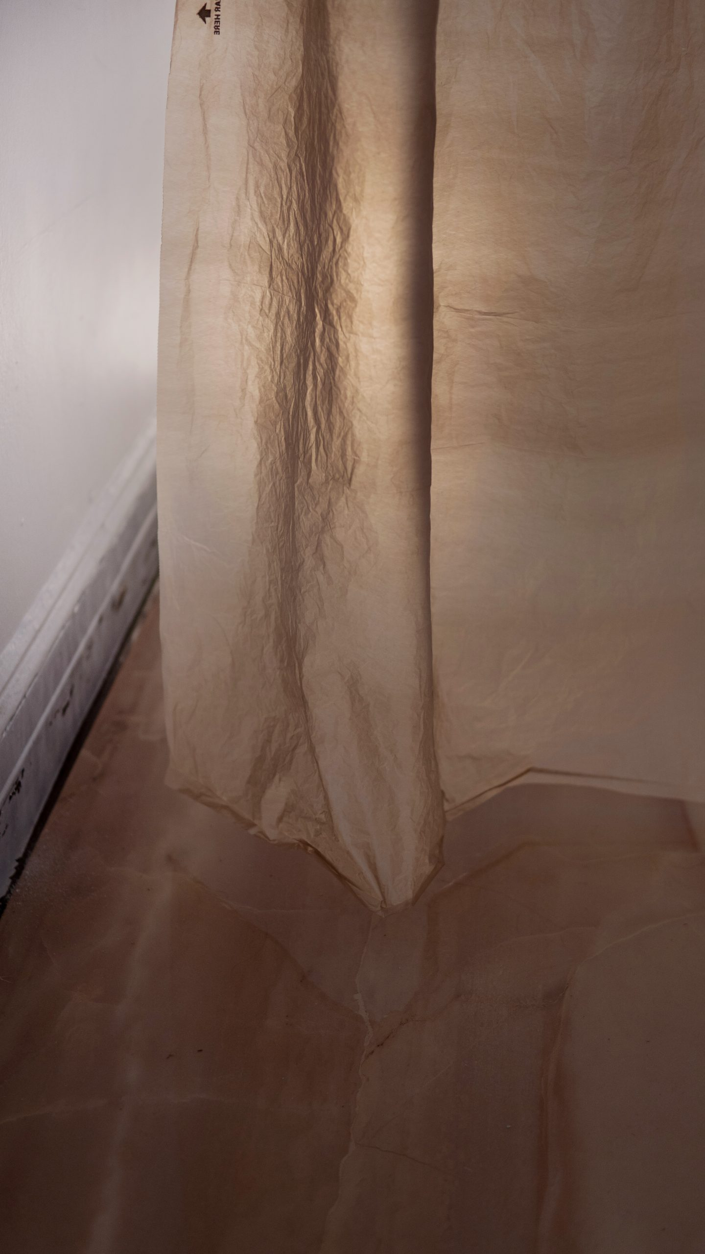 "Regina Viqueira, Installation documentation of ""Luxury Plastic"", plastic Lowe's bag, shower curtain rings, rope wire, hooks, large format tile, clamp light, dimensions variable"